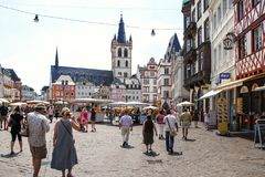People walk on Hauptmarkt square in Trier city. TRIER, GERMANY - JUNE 28, 2010: people walk on Hauptmarkt Main Market square and view of St Gangolf Church in Royalty Free Stock Photography