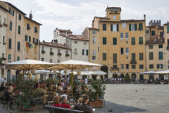 People walk and have a rest in cafes along Amphitheatre square. Stock Image
