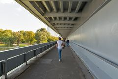 People walk inside UFO bridge in Bratislava, Slovakia. People walk inside New bridge over Danube river. With a population of about 450 000, Bratislava is one of Stock Images