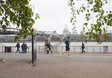 People walk and jog near millennium bridge along river thames in Royalty Free Stock Images