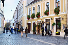 People walk on a narrow street with cobblestone pavers in the old historic town center Stock Photography
