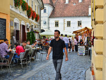 People walk on a narrow street with outdoor restaurant cafe Stock Photo