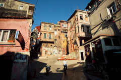 People walk near the broken walls of poor street of Istanbul Royalty Free Stock Images