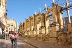 People walk near old ruined opera house in Valletta royalty free stock photography