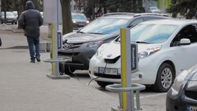 People walk near parked electric vehicle connected to charger by cable. The inscription hashtag advertises Oschadbank at action. stock video footage
