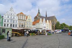 People walk by the New Market square in Rostock, Germany. Stock Image