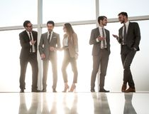 People walk in the office on the sunny background. Young businessmen are standing in modern office with panoramic windows royalty free stock photos