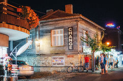 People walk through the old town at night. Currency exchange in a typical wooden house in ancient town of Nessebar. Stock Photo