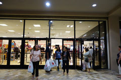 People walk out of Macy's store with shopping bags on Grey thurs. HONOLULU, HI - NOVEMBER 27: People walk out of Macy's store with shopping bags on Grey thursday Stock Photography