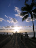 People walk out to Pier to watch Sunset in Waikiki Stock Images