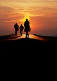 People walk over bridge in sunset Stock Photography