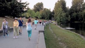 People walk in the park next to a lake Stock Photo