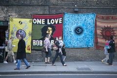 People walk past the large shawls for sale, hanging on a brick wall. Camden Town Royalty Free Stock Photography