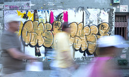 People Walk past NYC Street Art CASH Graffiti - Grey pink & yellow. Blurred people walking quickly on the street pass by layers of urban decay Street Art and Royalty Free Stock Image