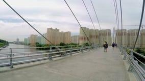 People walk on a pedestrian bridge across the river in Krasnogorsk stock video footage
