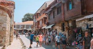 People walk through pedestrian cobblestone streets of ancient Nessebar stock footage
