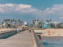 People walk on the pier and sunbathe on the beach. View from Venice Beach Pier.  Stock Photo