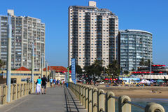 People Walk on Pier Towards City Skyline. DURBAN; SOUTH AFRICA - MAY 3; 2014: People walk along concrete pier towards commercial and residential buildings on royalty free stock photos