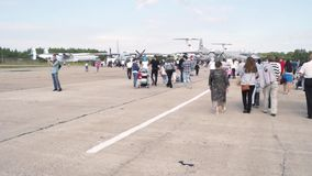 People walk between the planes at the open day at the aerodrome Migalovo stock footage