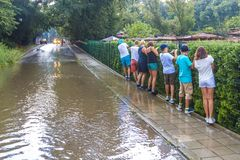 Flooding after heavy rain, tourists bypass puddle along  edge of sidewalk, following each other in row, holding onto fence, Bulgar. People walk through puddles Royalty Free Stock Images