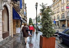 People walk during rain on avenue Louise in Brussels Royalty Free Stock Photo