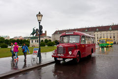 People walk on rainy street past the antique touristic bus Royalty Free Stock Photos
