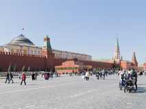 People walk on Red Square. Moscow - April 12, 2015: Citizens and tourists walking on Moscow's Red Square and Lenin's mausoleum is visible and the Senate, in good royalty free stock photos