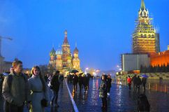 People walk on the Red Square in Moscow. Rainy evening. Stock Image
