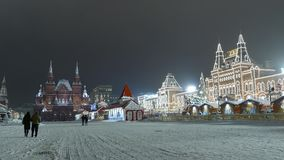 People walk by Red Square near GUM adorned with garlands. stock video