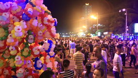 people walk about resort city streets at festival at night stock video