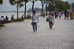 People walk at riverbank Stock Photo