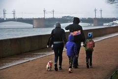 People walk in Saint Petersburg under umbrella stock photo