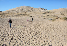 People walk on the sand of the Mojave Desert. People walk at the Kelso Sand Dunes in the Mojave Desert, Western United States Stock Photo
