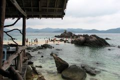 People walk in the sea near the coast surrounded by huge stones against the backdrop of the mountains, Thailand royalty free stock images