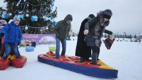 People Walk on Snow with Blown Snowmobiles near Christmas Tree. KAZAN, TATARSTAN/RUSSIA - DECEMBER 13 2016: Children and adults walk on snow with blown stock video