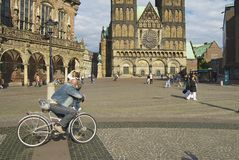 People walk by the square with the historic town hall and the cathedral in the background in Bremen, Germany. Stock Photo