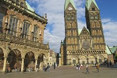 People walk by the square with the historic town hall and the cathedral in the background in Bremen, Germany. Royalty Free Stock Photos
