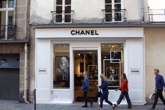 People walk by a store of famous, international French luxury brand`s store royalty free stock images