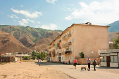 People walk on the street in four-storey house in a small town between the mountains Stock Images