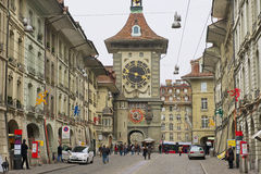 People walk by the street with the historic Bern Clock tower at the background in Bern, Switzerland. Stock Photography