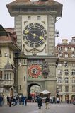 People walk by the street with the historic Bern Clock tower at the background in Bern, Switzerland. BERN, SWITZERLAND - FEBRUARY 23, 2012: Unidentified people Stock Photo