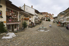 People walk by the street of the medieval town of Gruyeres, Switzerland. Stock Images