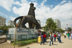 People walk by the street next to the iconic statue of the Lion of Judah in Addis Ababa, Ethiopia. ADDIS ABABA, ETHIOPIA - JANUARY 18, 2010: Unidentified people Stock Photo