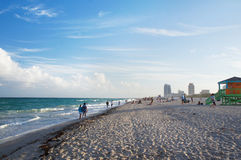 People walk at the sunny South Beach of Miami Royalty Free Stock Image