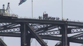 People walk on Sydney Harbor Bridge in distance stock video footage