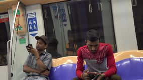 People walk at the train station in Singapore. Unidentified men sit on the Mass Rapid Transit train in Singapore. MRT is a rapid transit system forming the major stock video footage