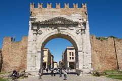 People walk under Augustus Arch - the ancient romanesque gate and the historical landmark of Rimini, Italy. Stock Photos