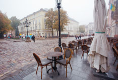 People walk under rain at Market Square with cobbled streets and empty outdoor cafe Royalty Free Stock Images