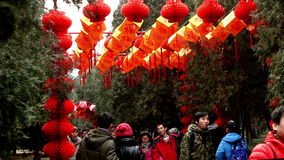 People walk under the red lanterns at Ditan temple fair during Spring Festival in Beijing, China.  stock video footage