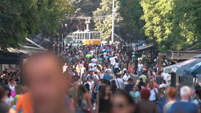 Crowded street with people and a tram car stock video footage